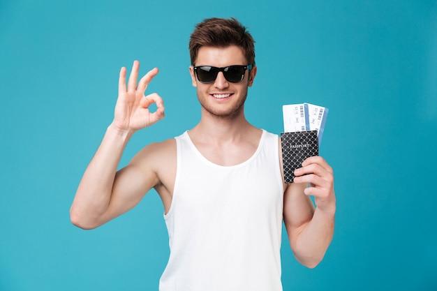Homem segurando o passaporte com bilhetes de avião e mostrando o gesto ok