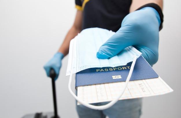 Homem segurando o passaporte com passagem de trem e máscara médica na mão
