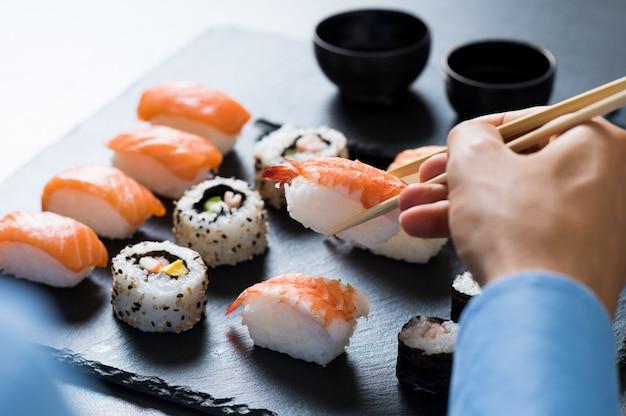 Homem segurando o pauzinho e comendo sushi no restaurante