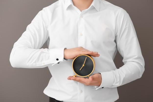 Homem segurando o relógio no fundo cinza. conceito de gerenciamento de tempo