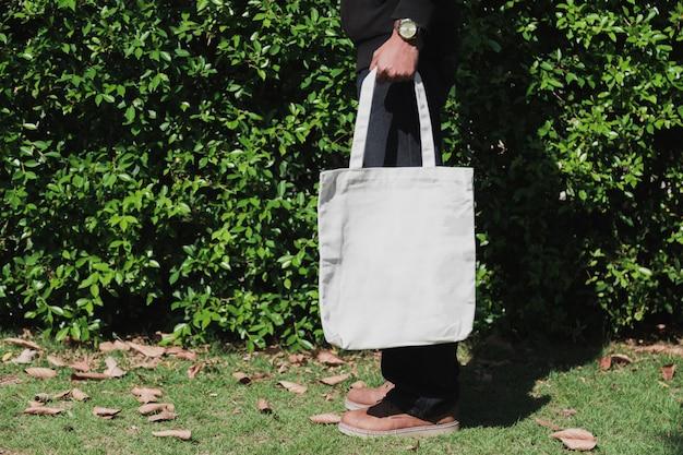 Homem segurando o saco de lona para maquete, conceito de ecologia.