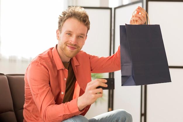 Homem segurando o saco e cartão de crédito