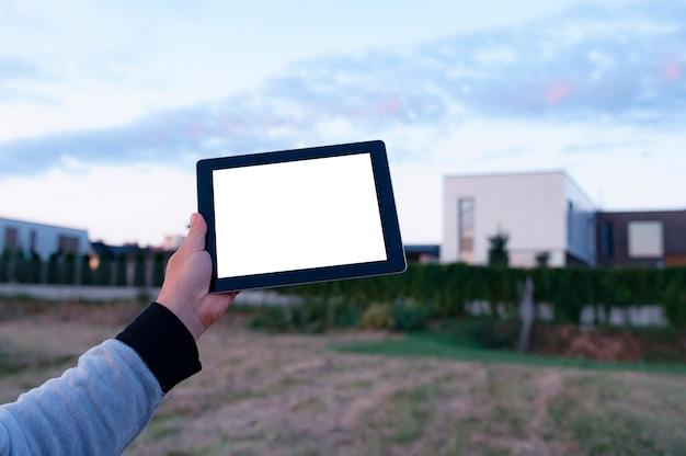 Homem segurando o tablet preto na mão com tela branca em branco na vizinhança
