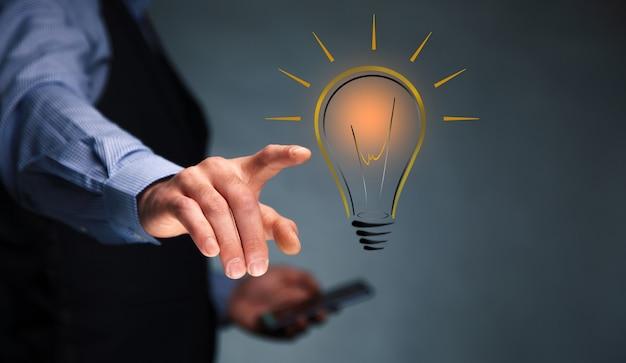 Homem segurando o telefone com uma ideia ou lâmpada