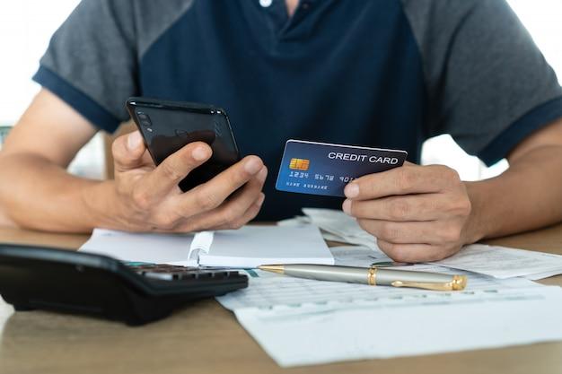 Homem segurando o telefone móvel e cartões de crédito, conta e conceito de poupança.