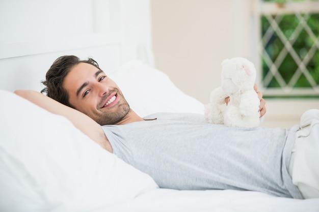 Homem segurando o ursinho de pelúcia enquanto relaxa na cama