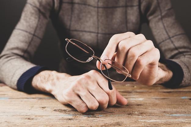 Homem segurando óculos ópticos