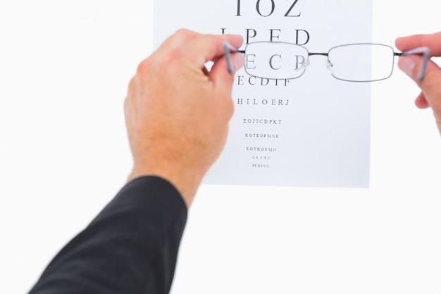 Homem, segurando, óculos, sobre, papel