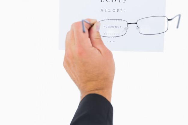 Homem segurando óculos sobre papel