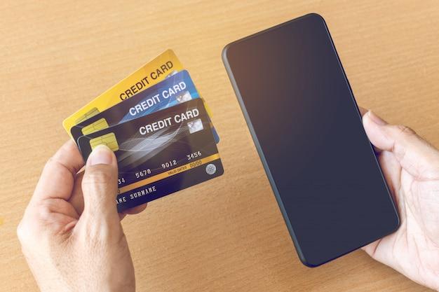 Homem segurando os cartões de crédito e smartphone. compras on-line na internet usando um smartphone