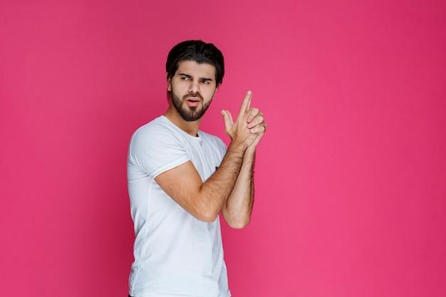 Homem segurando os dedos como uma arma.