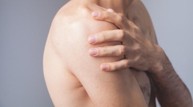 Homem segurando os ombros com dor no ombro