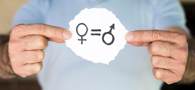 Homem segurando papel com símbolos de gênero