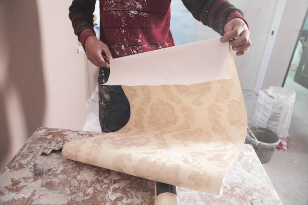 Homem segurando papel de parede em processo de renovação