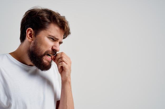 Homem segurando para enfrentar a dor na luz de fundo dos dentes