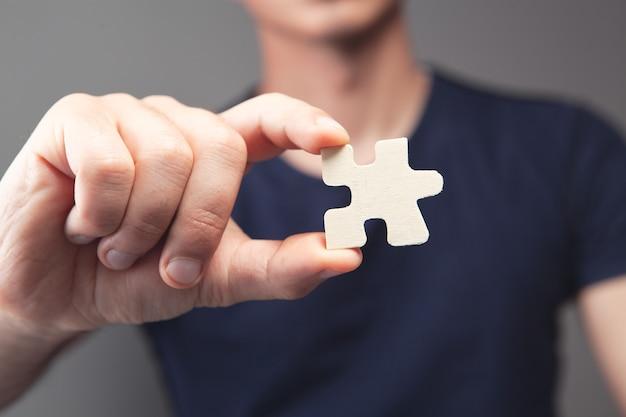 Homem segurando peça do quebra-cabeça