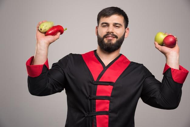 Homem segurando pimenta vermelha, maçãs e abobrinha.