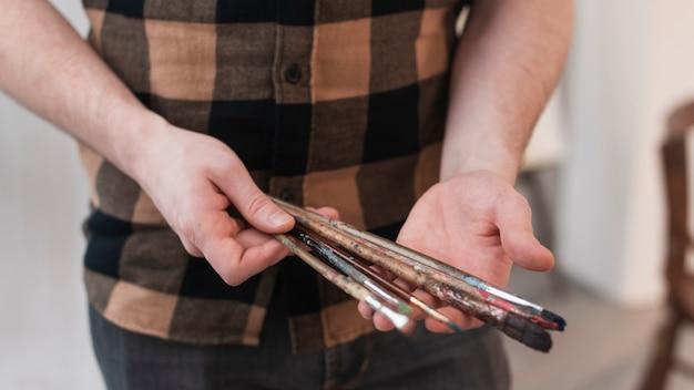 Homem segurando pincéis de pintura
