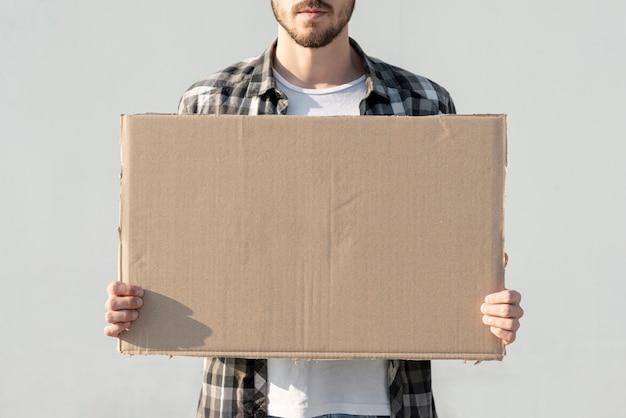 Homem segurando placa com maquete