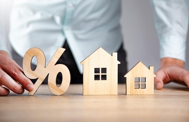 Homem segurando porcentagem com modelos de casas