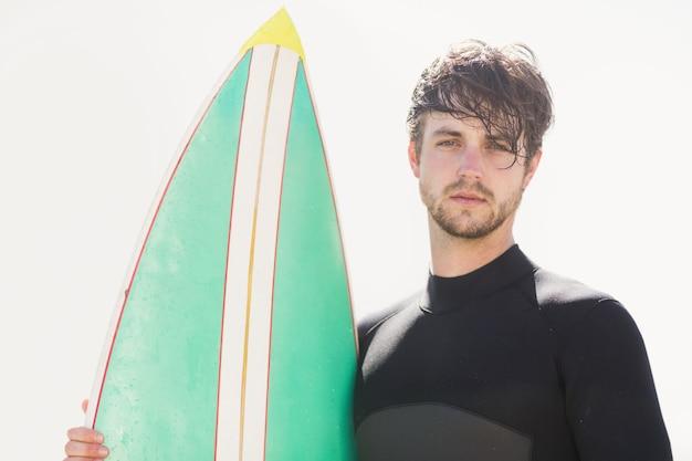 Homem segurando prancha de surf na praia
