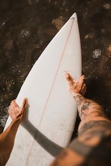 Homem, segurando, prancha surf, ligado, água, perto, costa