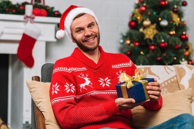 Homem, segurando, presente, caixa, ligado, sofá