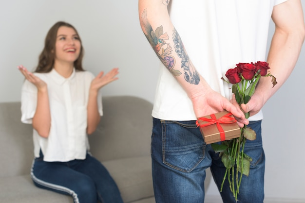 Homem, segurando, presente, para, mulher jovem, costas