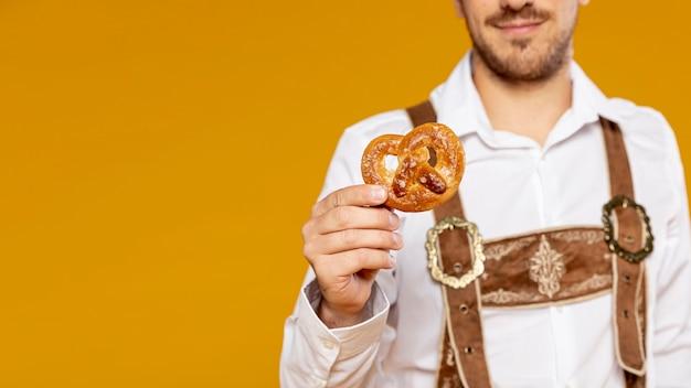 Homem, segurando, pretzel, com, espaço cópia