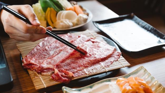 Homem segurando rara fatia wagyu a5 carne por pauzinhos para ferver em panela quente de shabu.