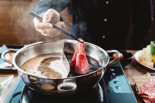 Homem, segurando, raro, fatia, wagyu, a5, carne, em, shabu, pote quente, shoyu, base sopa, por, chopsticks