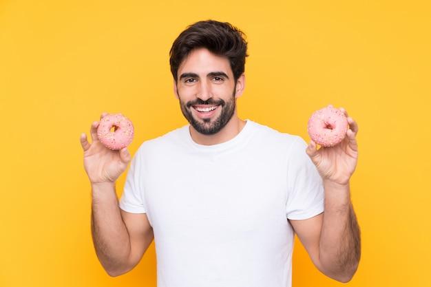 Homem segurando rosquinhas sobre parede amarela