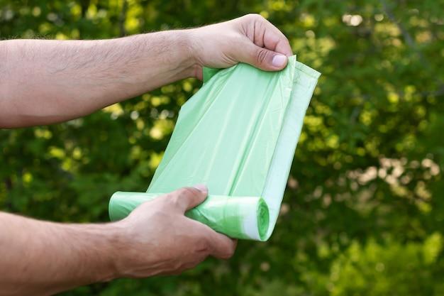 Homem segurando saco plástico ecológico de lixo bio em rolo ao ar livre, saco para compostagem de lixo orgânico