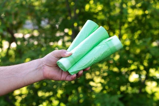 Homem segurando sacos plásticos ecológicos de lixo bio em rolos ao ar livre