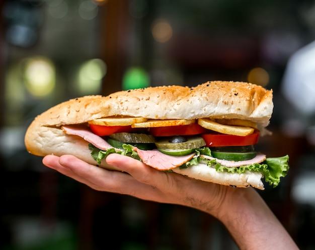 Homem, segurando, sanduíche, vista lateral