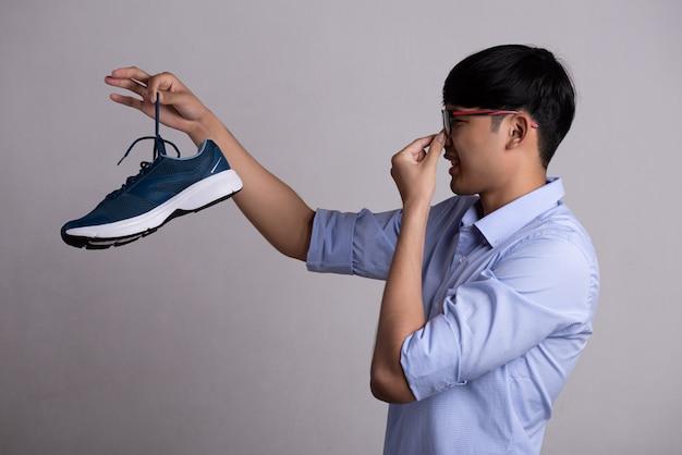 Homem segurando sapato fedido sujo com uma expressão de nojo.