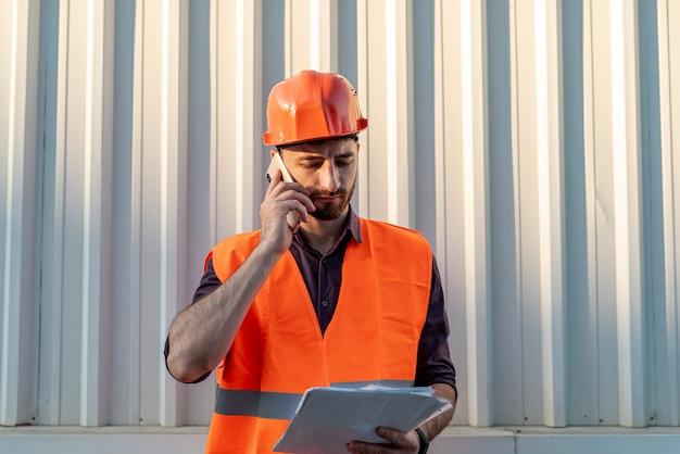 Homem, segurando, schematics, e, conversa telefone