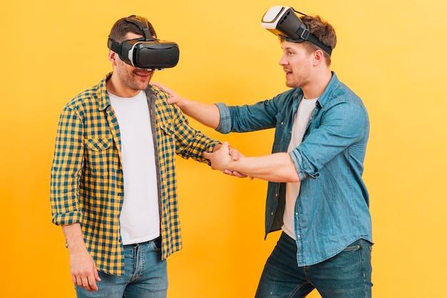 Homem segurando seu amigo usando óculos de realidade virtual em fundo amarelo