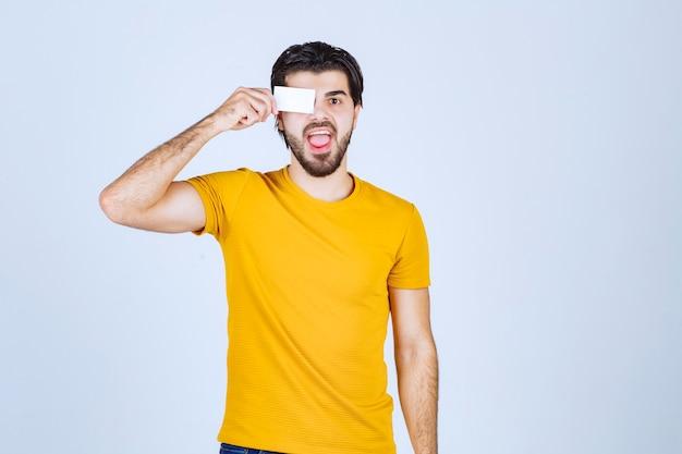Homem segurando seu cartão de visita aos olhos.