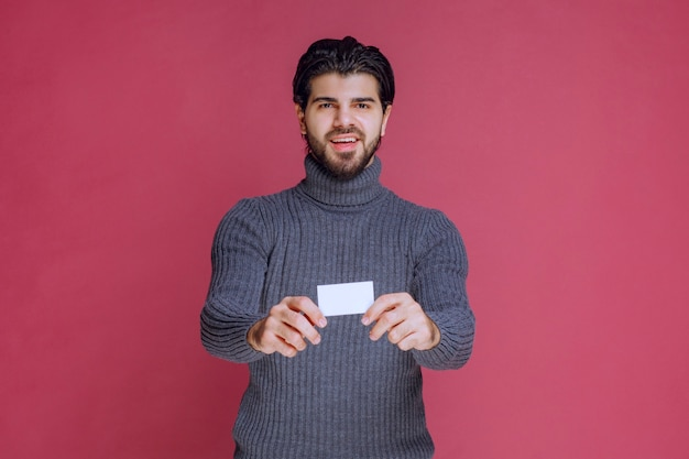 Homem segurando seu cartão de visita, apresentando ou recebendo.