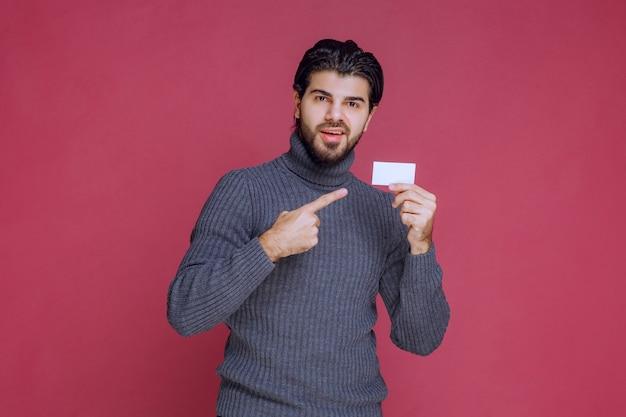 Homem segurando seu cartão de visita e apontando para ele.