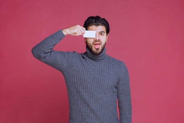 Homem segurando seu cartão de visita e colocando-o no olho dele.