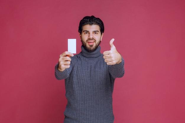 Homem segurando seu cartão de visita e faz sinal positivo com a mão.