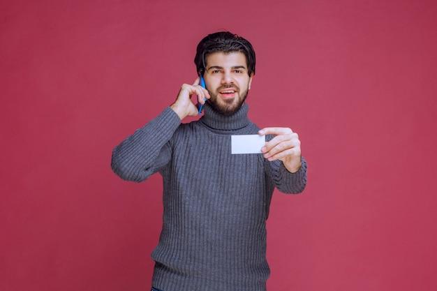 Homem segurando seu cartão de visita e ligando para o número de contato nele.
