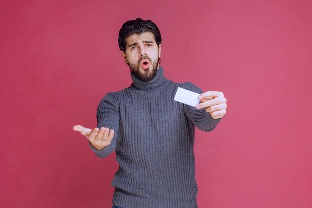 Homem segurando seu cartão de visita e parece surpreso.