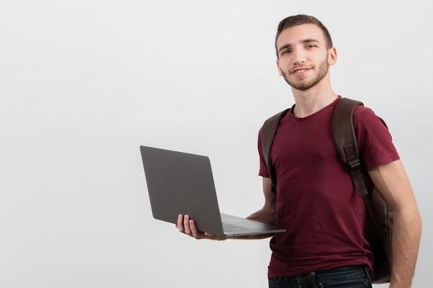 Homem segurando seu laptop e olhando para a câmera