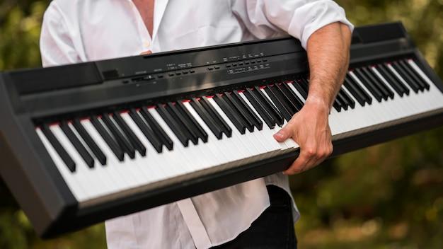 Homem segurando seu piano digital