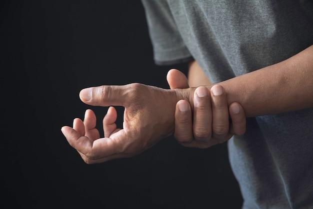 Homem, segurando, seu, pulso dor em um pulso de homem. homem massageando o pulso doloroso.