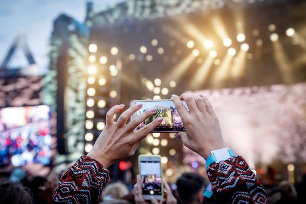 Homem segurando seu telefone inteligente e fotografando o show.