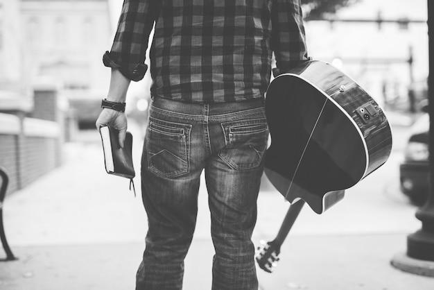 Homem segurando seu violão e uma bíblia com uma marca em preto e branco